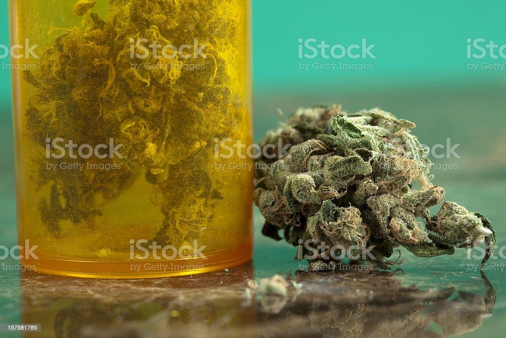 Close-up of medical marijuana with orange jar full with it stock photo