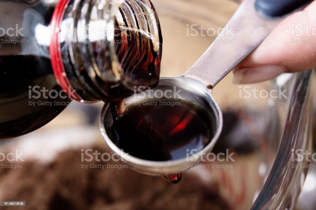 Close-up de medicina sendo derramada sobre uma colher de chá - foto de acervo