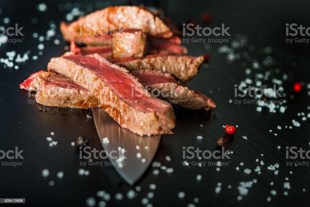 Closeup of medium rare steak slices on a knife stock photo