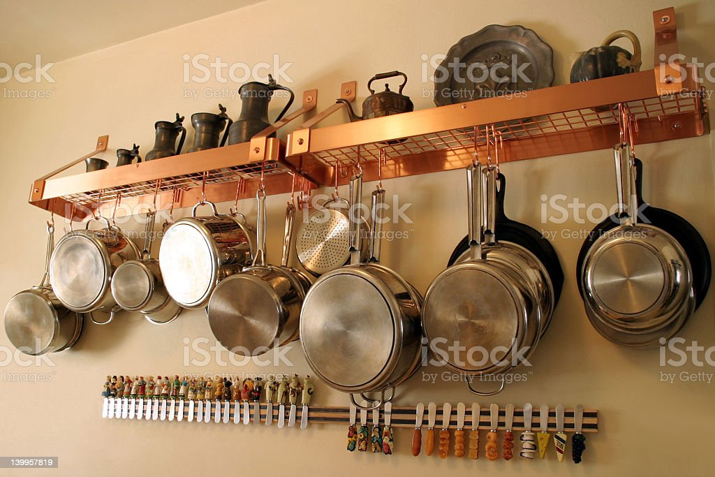 Close-up of metal pots and Pans hanging on the kitchen wall stock photo