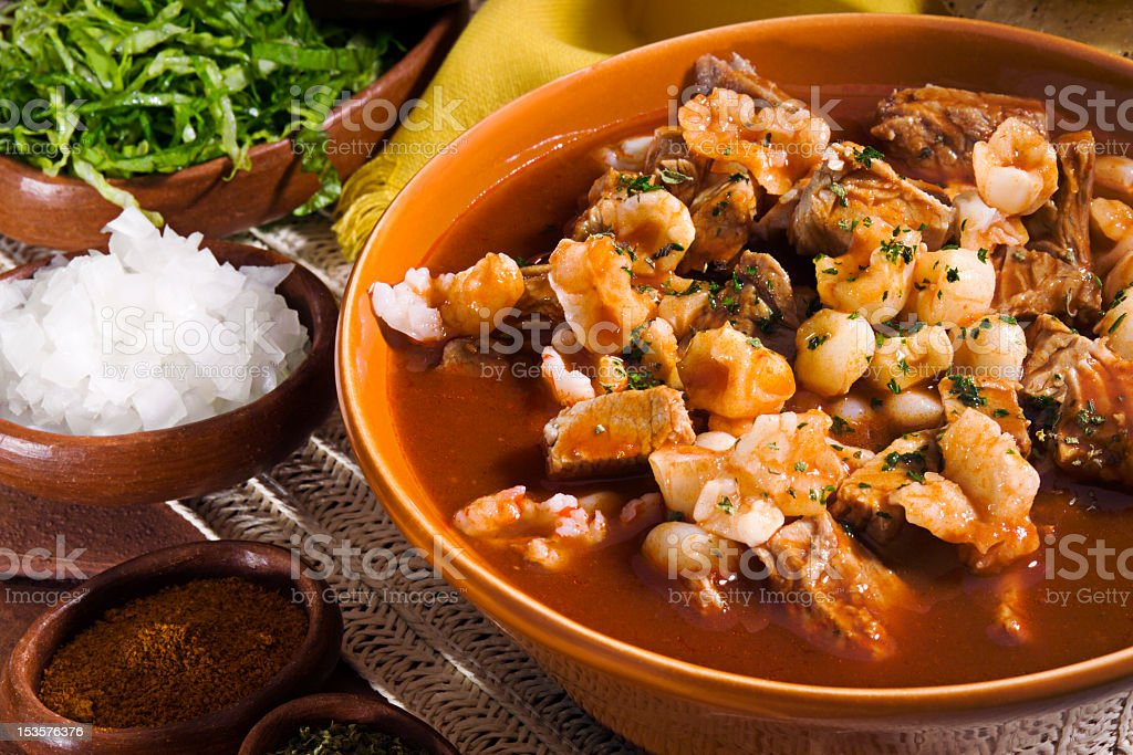 Close-up of Mexican red pozole served in orange bowl stock photo