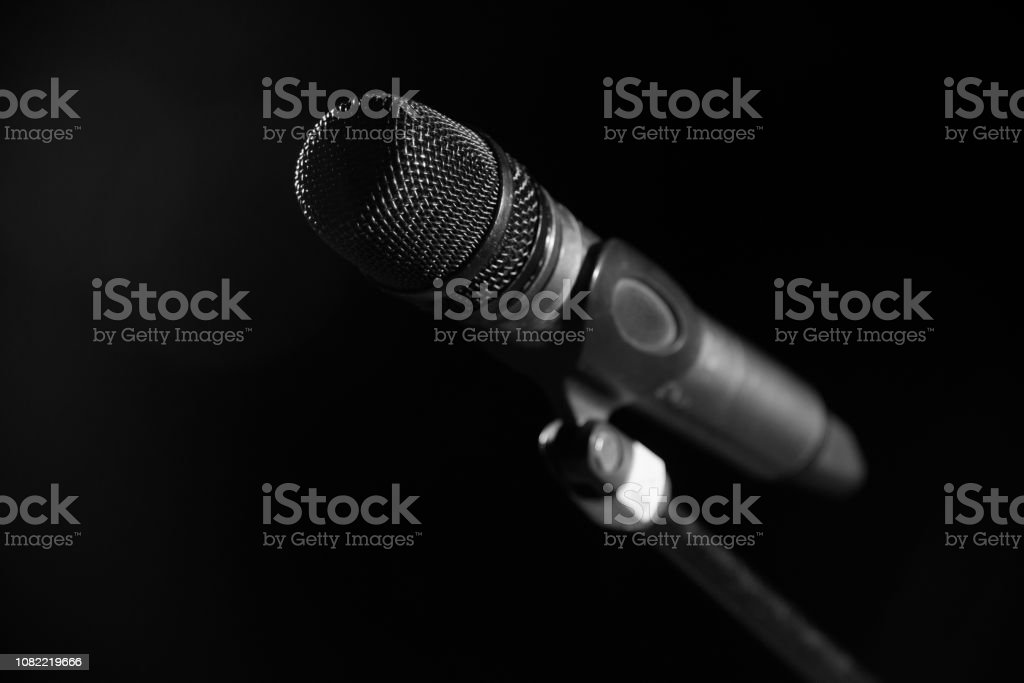 Closeup of microphone in concert hall or conference room on dark hall...