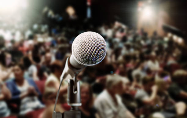 Close-up of microphone with spot lit, defocused audience stock photo