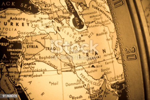 Cross-processed closeup shot of the Middle East region on an old globe. The longitudinal metal bar can be seen to the right of the image.