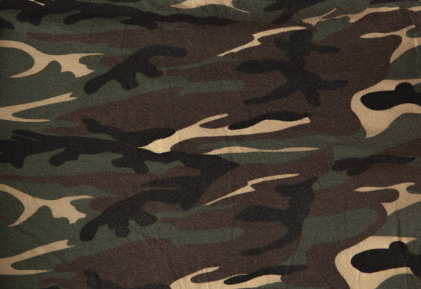 Closeup of military uniform surface. Texture of fabric, close-up, military coloring Closeup of military uniform surface. Texture of fabric, close-up, military coloring. camouflage stock pictures, royalty-free photos & images