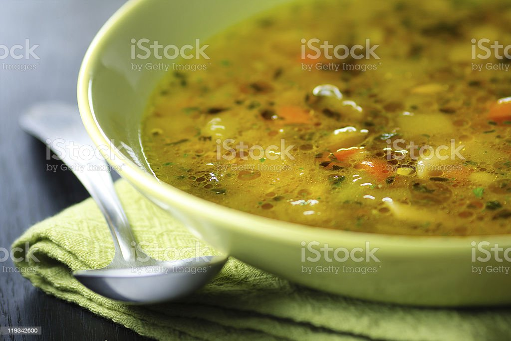 Close-up of minestrone soup in a plate with spoon nearby stock photo
