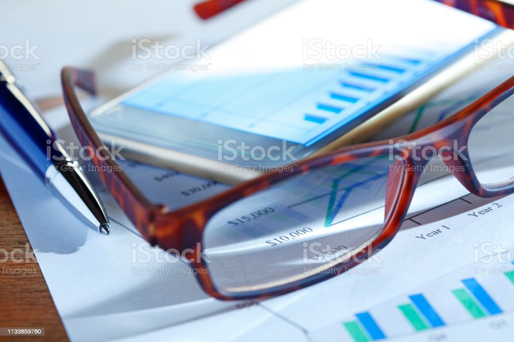 Closeup Of Mobile Device Through The Lens Of Pair Of Eyeglasses stock photo