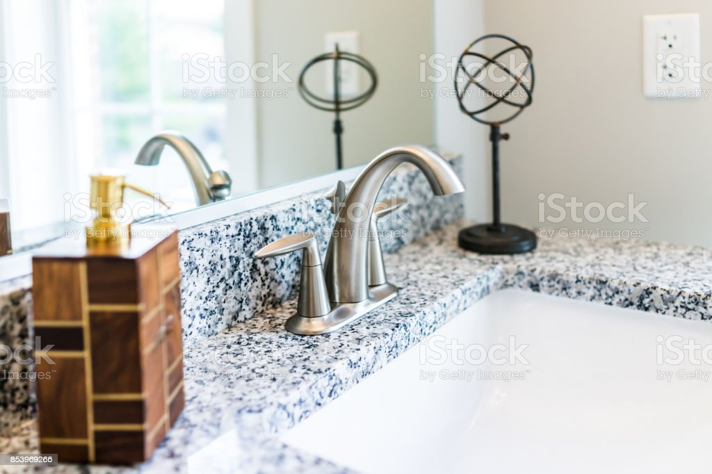 Closeup of modern bathroom sink with granite countertop, mirror, soap dispenser pump and faucet in staging model home, apartment or house stock photo