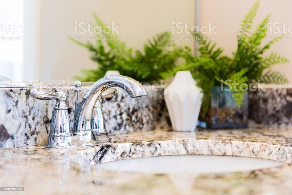 Closeup of modern bathroom sink with neutral granite countertop and mirror, green plant in pot stock photo