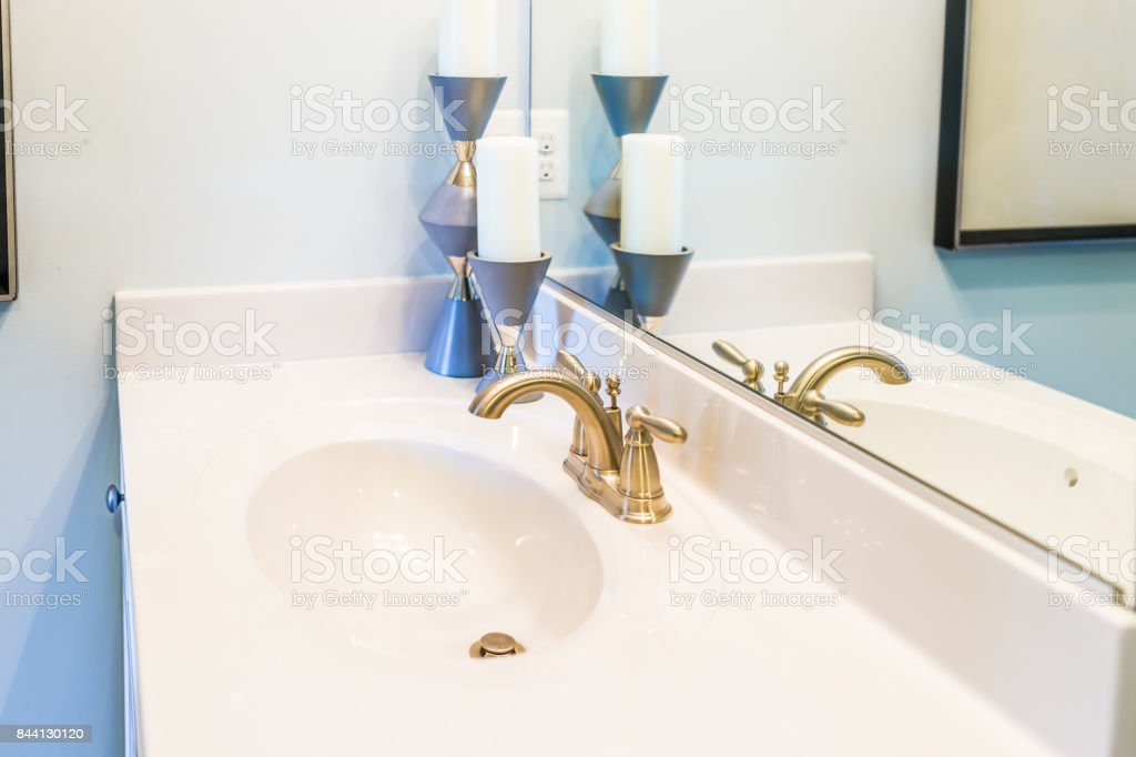 Picture of: Closeup Of Modern Bathroom Sink With White Countertop Mirror And Golden Faucet In Staging Model Home Apartment Or House Stock Photo Download Image Now Istock