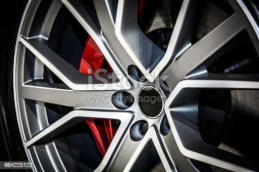 Close-up of modern alloy car wheel. The brake disc is visible behind of wheel bars.