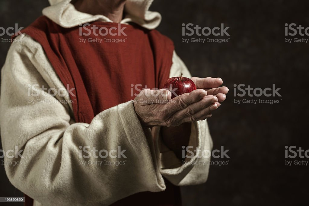 Close-up of monastic hands holding red apple. stock photo