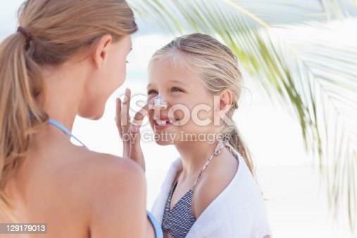 istock Close-up of mother applying suntan lotion on daughter's nose 129179013