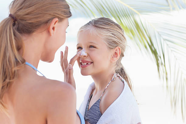 Close-up of mother applying suntan lotion on daughter's nose  suntan lotion stock pictures, royalty-free photos & images