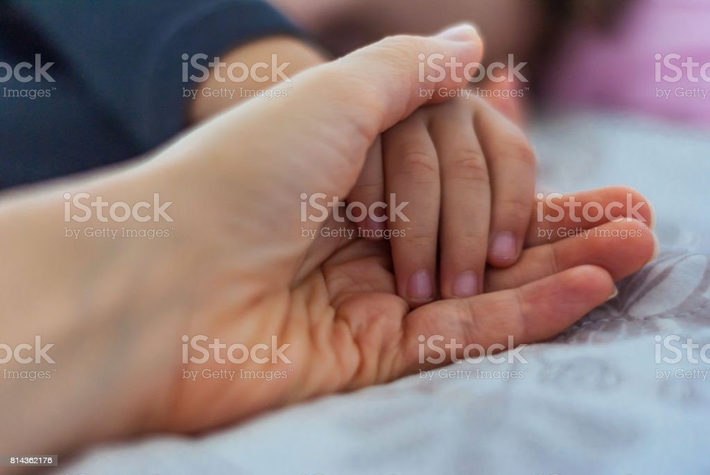 Close-up of mother\'s hand and sleeping and son. Love concept. Shallow...