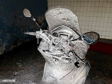 Close-up of motorcycle is washing with foam in garage. Horizontal composition. No people.