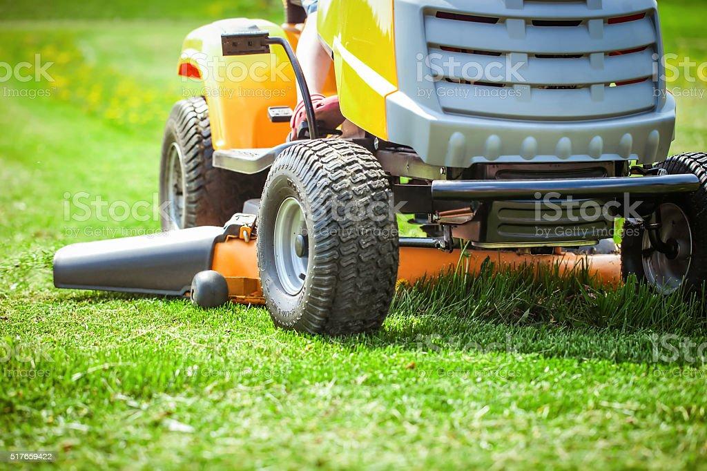 Closeup of mower cutting the grass stock photo