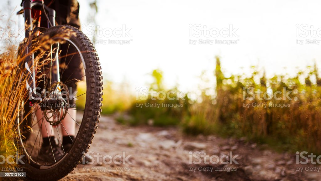 Close-up of MTB bike wheel on dirt road stock photo