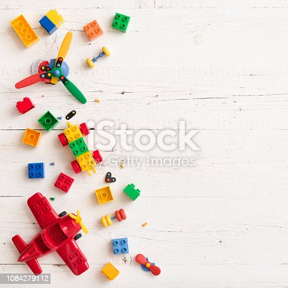 Closeup of multi-color plastic bricks on white wooden table or background. Early learning and development.