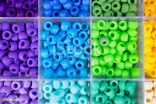 Close-up view of purple, blue, green and yellow colored beads inside a tray or plastic container. Each color is separated in its own section.  Arts and crafts projects or jewelry making activies.  No people in the image.  Great background.