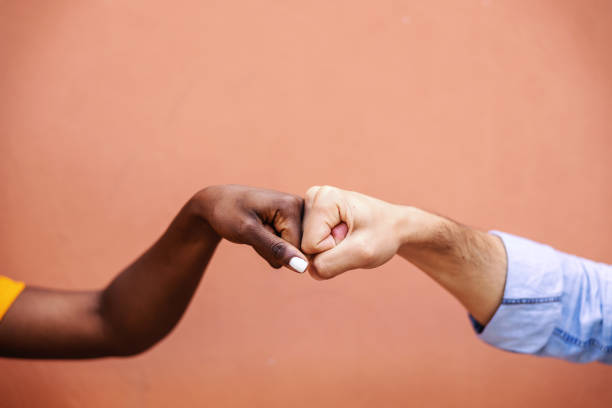 Closeup of multicultural friends giving fist bump to each other. stock photo