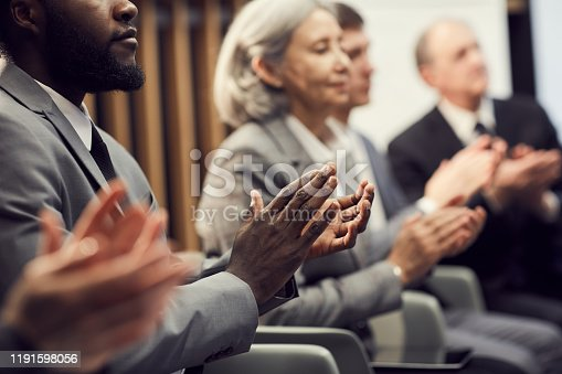 862720340 istock photo Close-up of multi-ethnic business people in formalwear sitting in row and applauding after presentation of speaker 1191598056