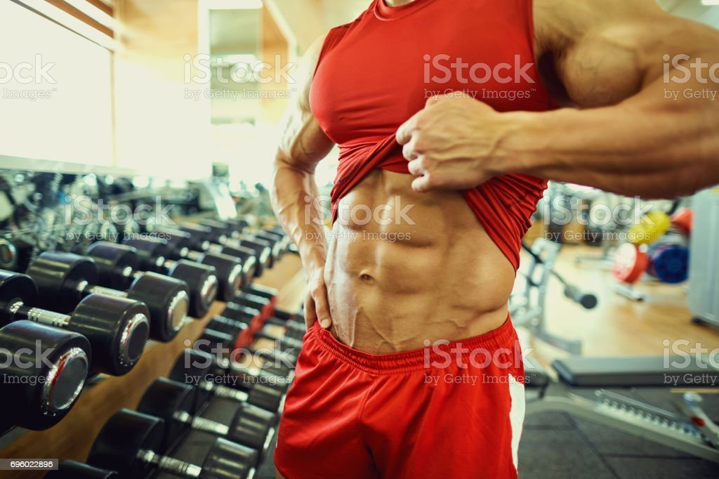 Close-up of muscle on  belly of a bodybuilder in the gym stock photo
