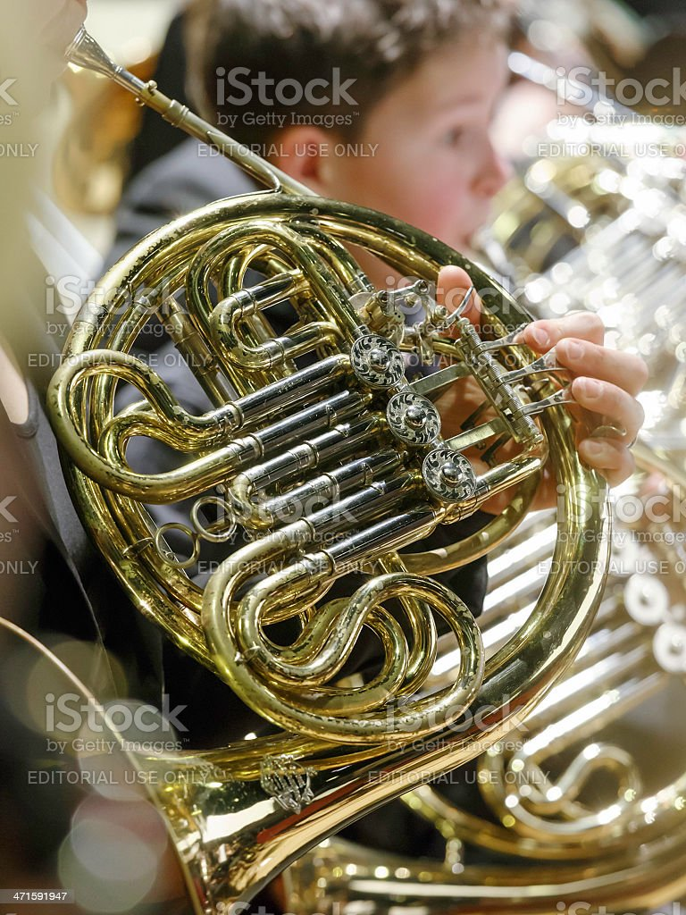 Close-up of musicians playing French horn in orchestra, indoor concert royalty-free stock photo