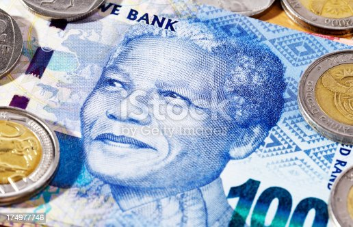 Close-up of a new South African One Hundred Rand banknote, featuring the smiling face of iconic statesman Nelson Mandela, with Five Rand and Two Rand coins scattered nearby.