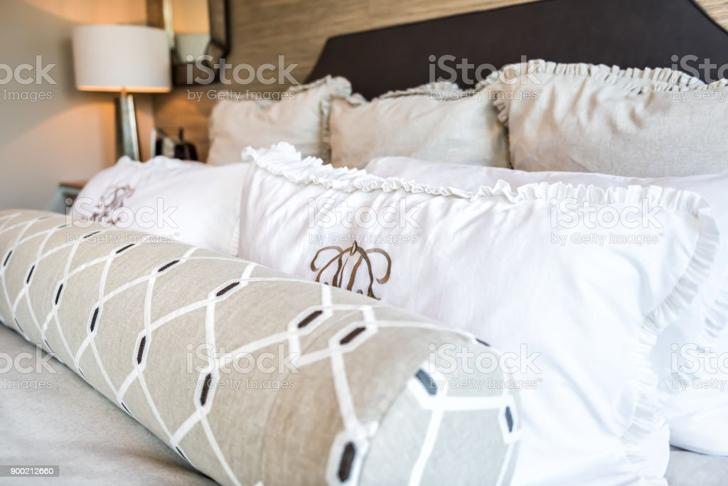 Closeup of new bed comforter with decorative pillows in bedroom in staging model home apartment or house stock photo
