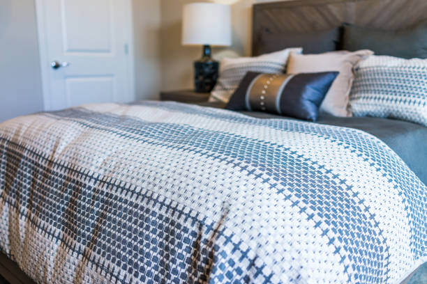 Closeup of new bed comforter with decorative pillows in bedroom Closeup of new bed comforter with decorative pillows in bedroom duvet stock pictures, royalty-free photos & images