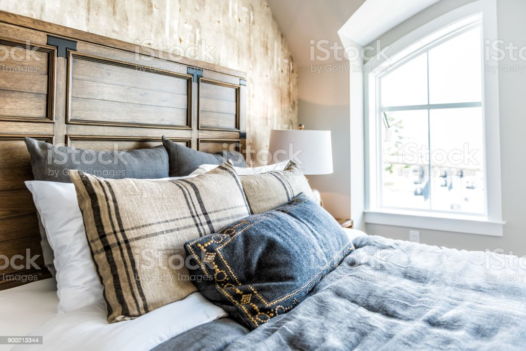 . Closeup Of New Bed Comforter With Headboard Side Table Lamp Decorative  Pillows In Bedroom In Staging Model Home House Or Apartment By Window With