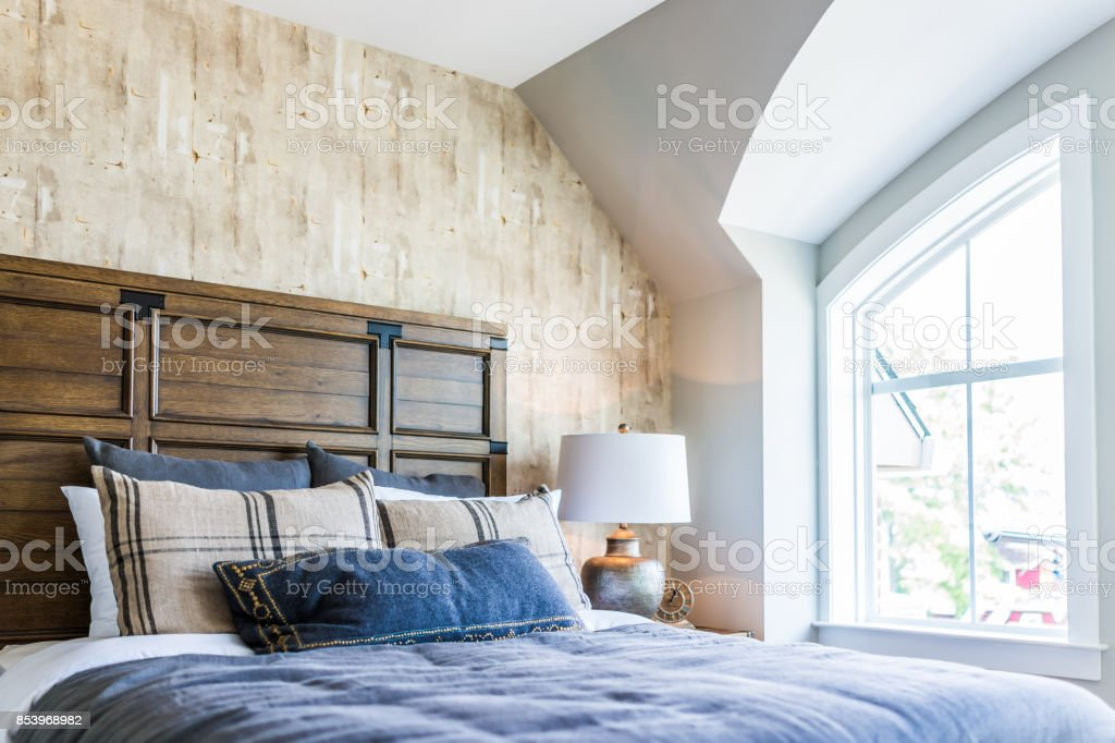 Closeup of new bed comforter with headboard, side table, lamp, vintage clock, decorative pillows in bedroom in staging model home, house or apartment by window with sunlight stock photo