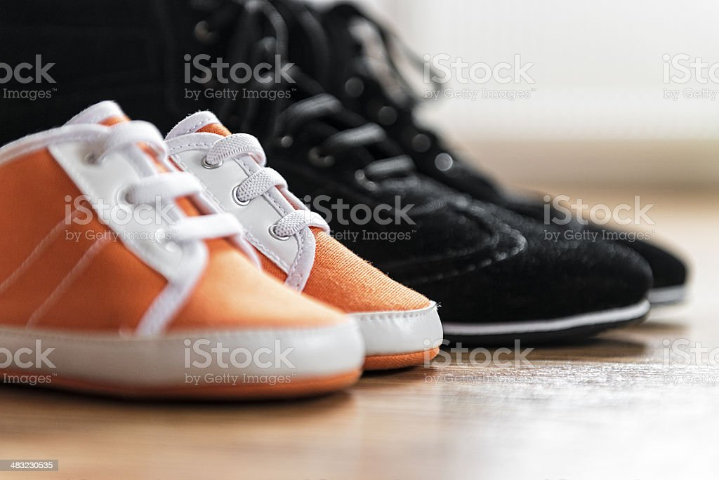 Close-up of newborn little baby booties against big father's shoes stock photo
