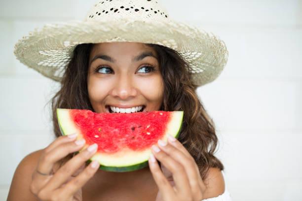 Close da bela mulher comendo fatia de melancia - foto de acervo