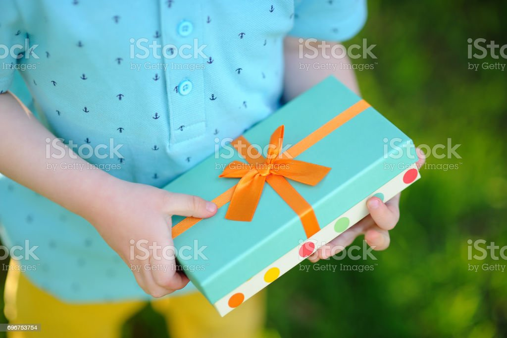 Close-up of nicely wrapped birthday gift being held by a child stock photo