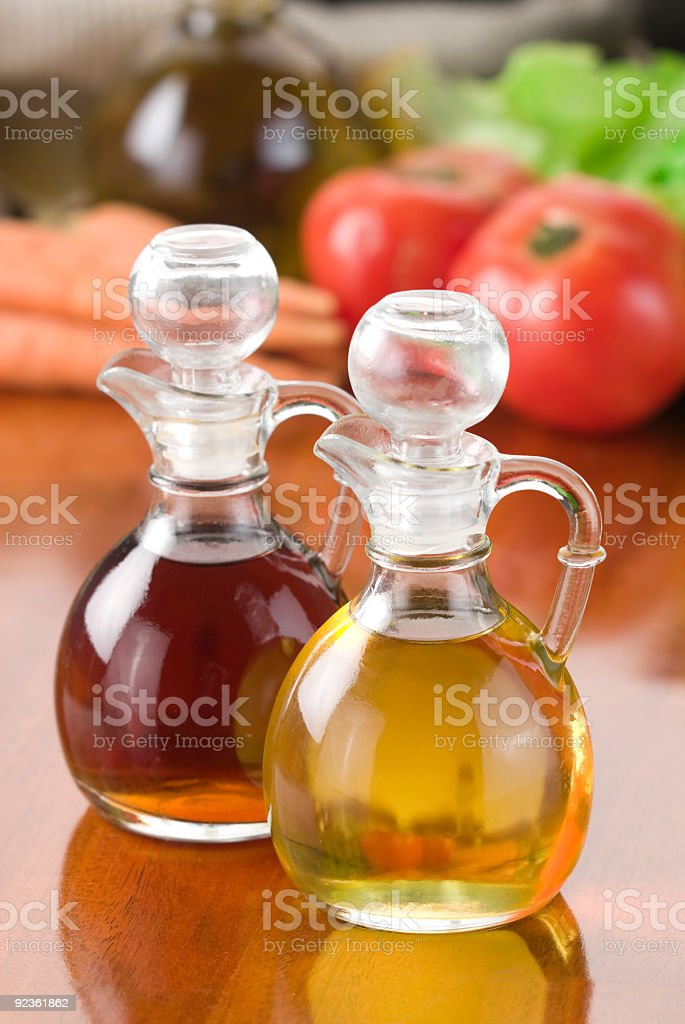 Close-up of oil and vinegar with tomatoes on the background royalty-free stock photo
