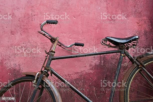Close-up of old black bicycle leaning against pink wall