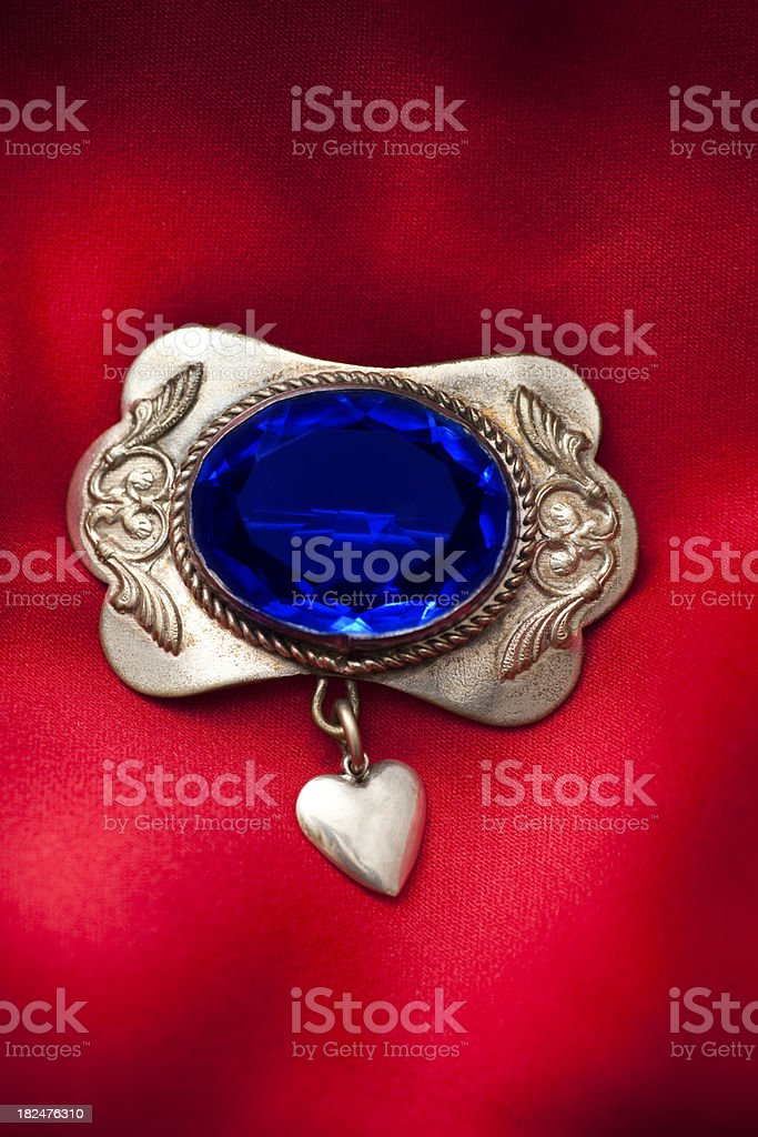 Closeup of old brooch with blue gem and heart royalty-free stock photo