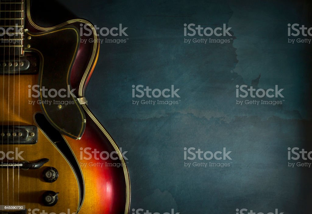 Close-up of old electric jazz guitar on a dark blue background stock photo