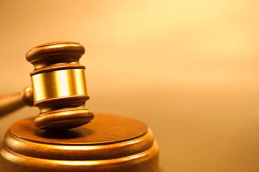 Closeup of an isolated wooden gavel on a blocked on a background