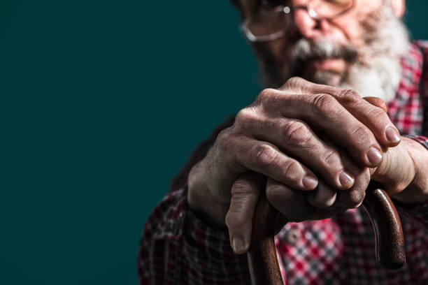 Close-up of old man's arthritic hands on cane stock photo