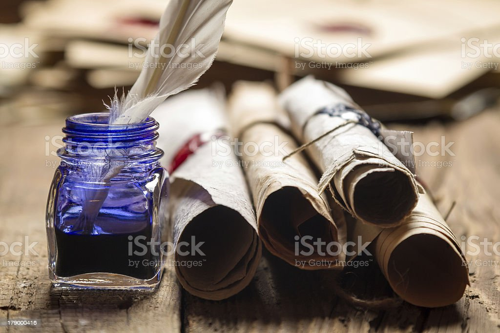 Closeup of old scrolls and blue ink in the inkwell stock photo