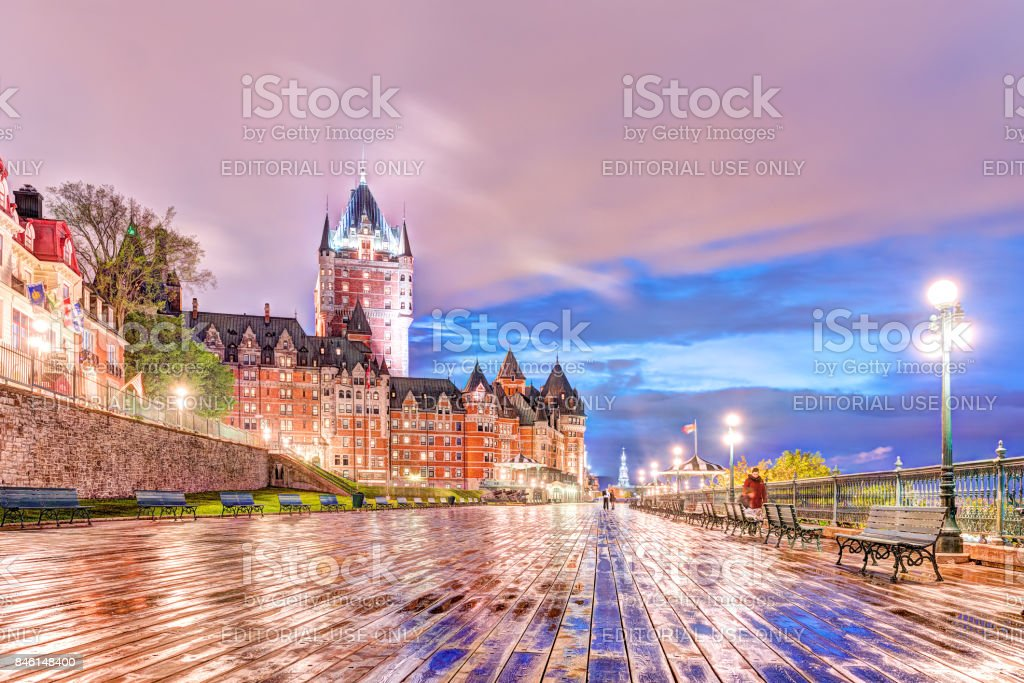 Closeup of old town ground level view of wet dufferin terrace boardwalk at night with Chateau Frontenac, purple clouds, city lights, lamps, lanterns and people stock photo