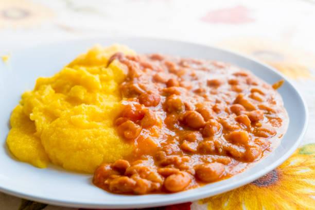 오래 된 전통적인 폴렌타 죽과 콩 이탈리아 농민 접시의 근접 촬영 - 폴렌타 죽 뉴스 사진 이미지