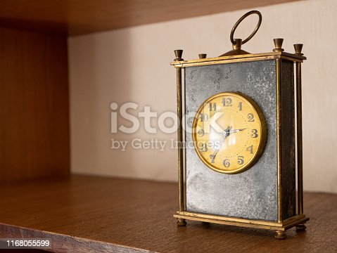 671883446istockphoto close-up of old vintage table black marble mechanic clock on wooden shelf with golden dial face and metallic circle for moving 1168055599