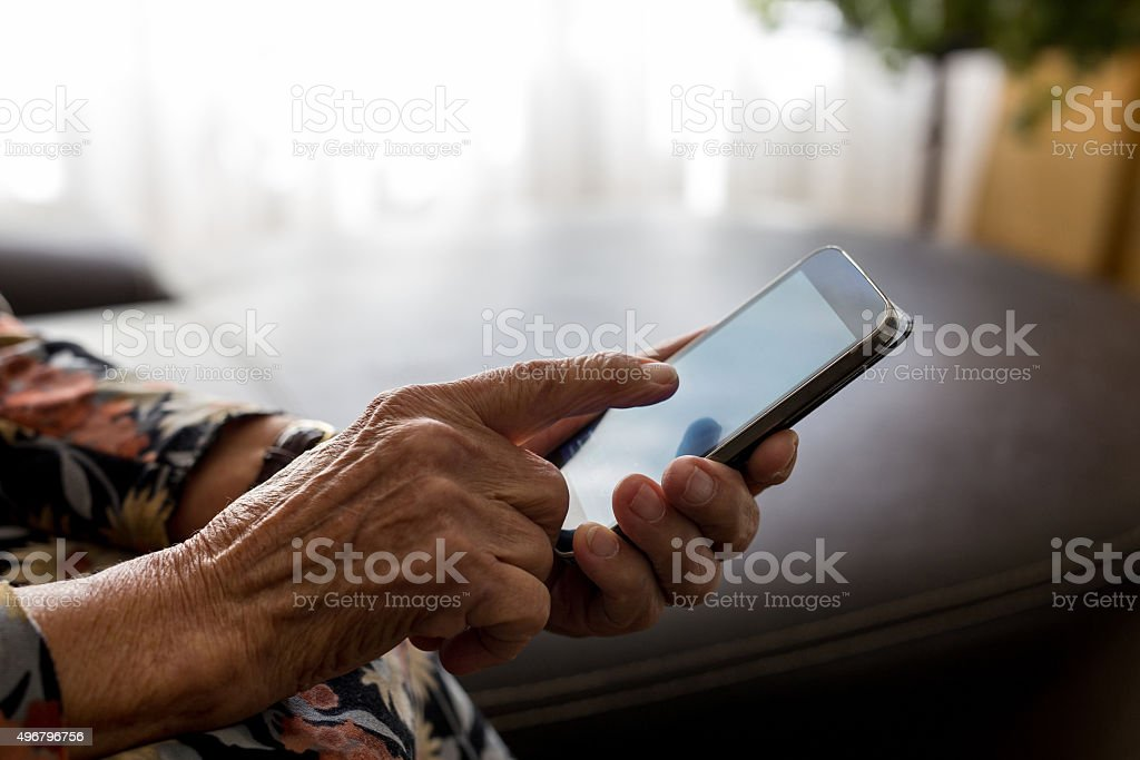 Closeup of old woman hands holding mobile phone stock photo