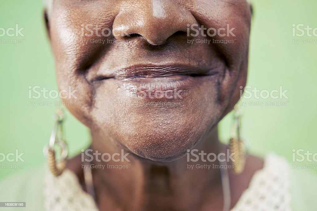 Closeup of old woman mouth against green background stock photo
