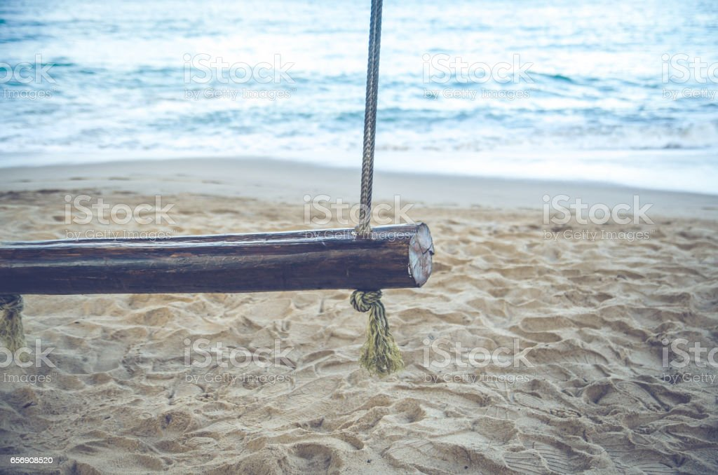 closeup of old wood swing with dirty rope on the sand beah , vintage tone style color stock photo