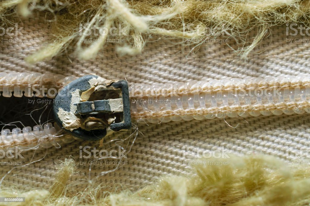 Close-Up Of Old Zipper Surrounded By Olive Green Fibers In Pattern stock photo